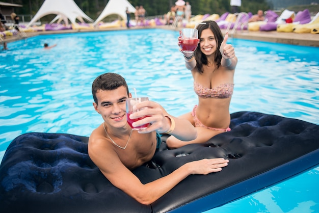 Man with woman enjoying with cocktails on the mattress at swimming pool