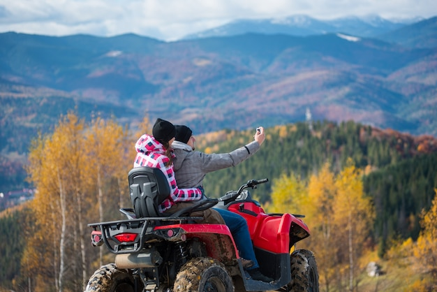 Man with woman on red quad bike