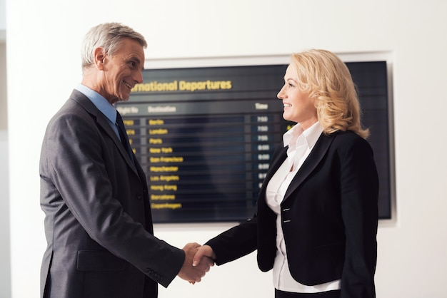 A man with a woman shakes hands near the timetable