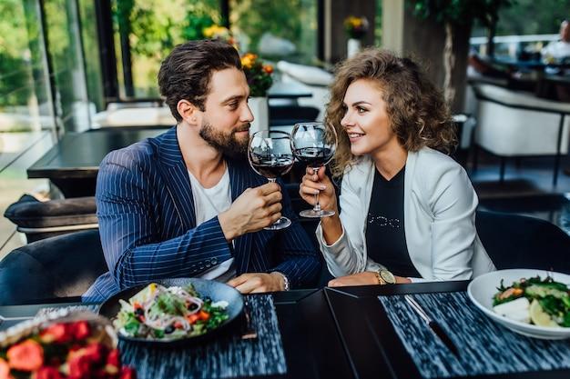 Мужчина с женщиной, сидящей за столом в кафе, пьет красное вино