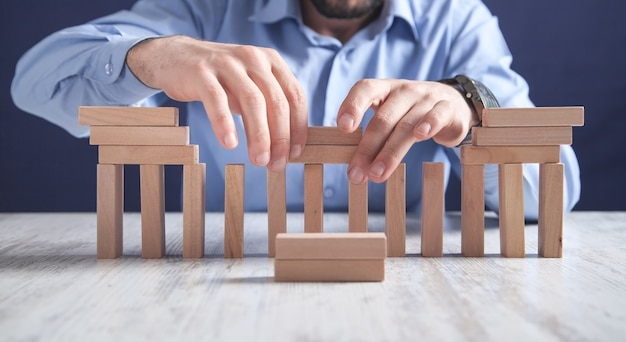 木製のブロックを持つ男。ビジネスコンセプト