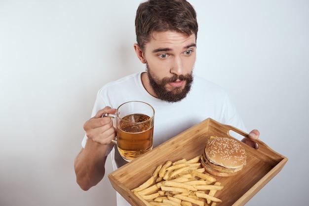 木製トレイビールジョッキフライドポテトとハンバーガーファーストフードカロリーモデルの白いtシャツを持つ男。