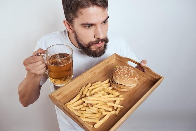 Человек с деревянным подносом, пивной кружкой, картофелем фри и гамбургером быстрого питания