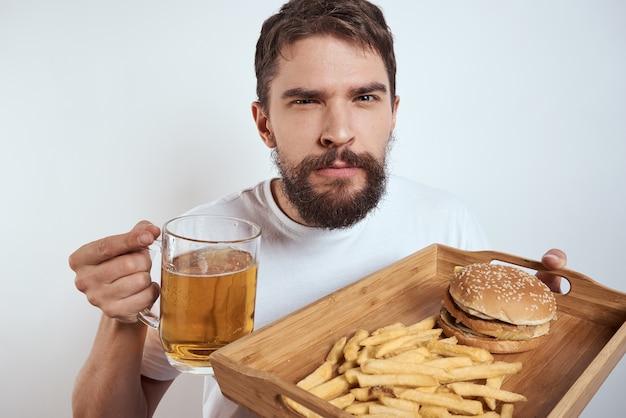 Человек с картофелем-фри кружки пива деревянного подноса и гамбургером.