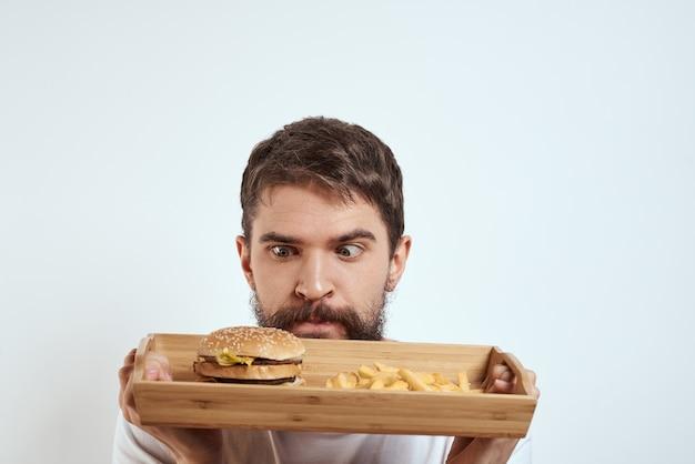 Человек с деревянным подносом фри и белой футболкой модели калорий гамбургера.