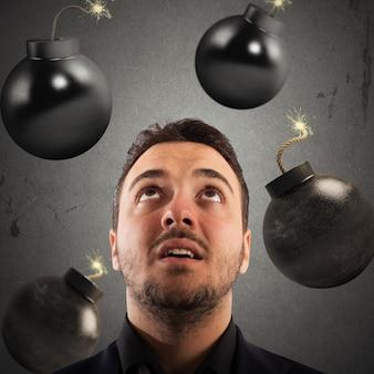 Человек с обеспокоенным выражением лица с падающими бомбами