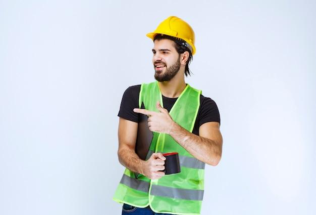 프로젝트 폴더와 커피 한 잔을 들고 노란색 헬멧을 쓴 남자.