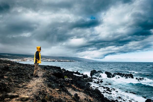 悪天候の挑戦で波の力を見て、旅行ライフスタイルの美しい景色を楽しんでいる海の海岸の野生の場所で黄色いジャケットを着た男 Premium写真