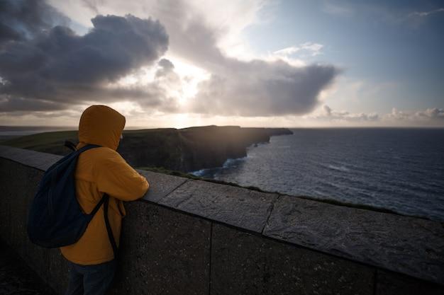 절벽의 moher에 수평선을보고 노란 재킷을 가진 남자