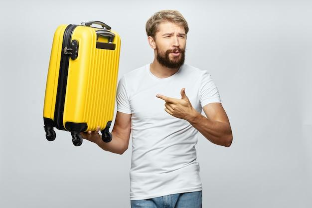 黄色いスーツケースの旅客空港旅行を持つ男