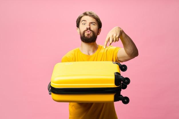 黄色のスーツケースの休暇の荷物の乗客のピンクの背景を持つ男