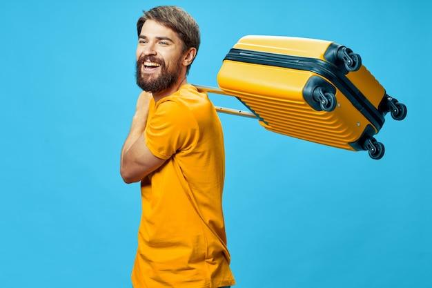 黄色のスーツケースを持つ男