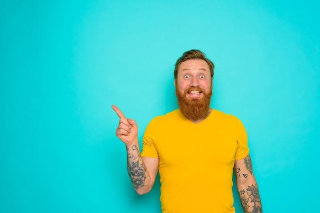 노란 티셔츠와 수염을 가진 남자는 무언가에 충격을 받았다