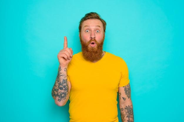 노란 티셔츠와 수염을 가진 남자는 무언가에 놀란다