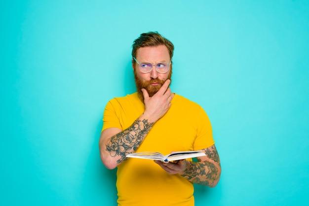 Человек в желтой футболке читает книгу