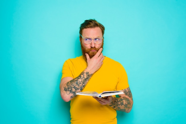 Man with yellow tshirt reads a book