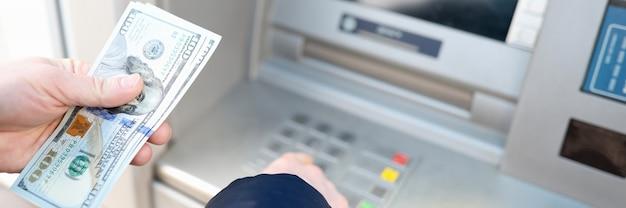 Atm 근접 촬영 뱅킹 서비스 개념에서 미국 달러를 인출하는 사람
