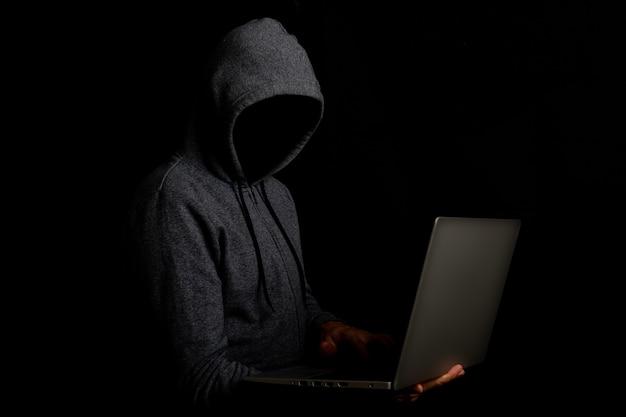 Человек без лица в капюшоне держит ноутбук на темноте