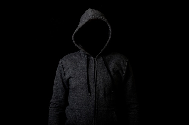 Человек без лица в капюшоне на темном фоне.