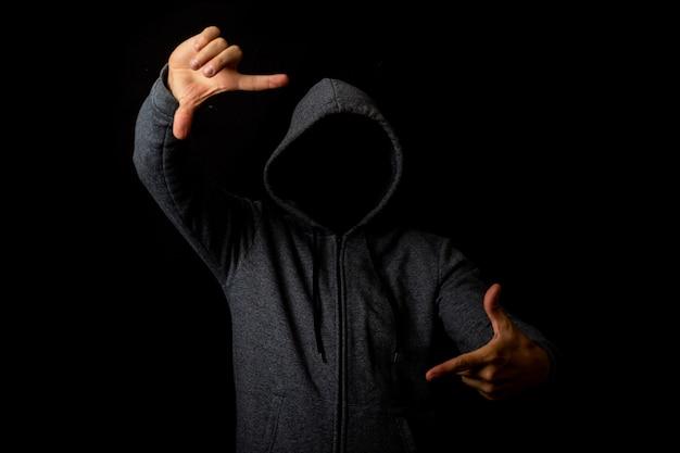 Человек без лица в капюшоне показывает зрителю что-то на темном фоне.