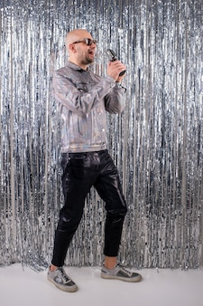 A man without hair with sunglasses in a shiny shirt, black leather pants and grey sneakers sings in a small silver microphone.