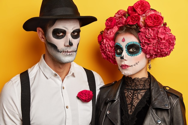 Man and woma wear skull makeup, black and white clothes, isolated over yellow background. serious vampires celebrate halloween together