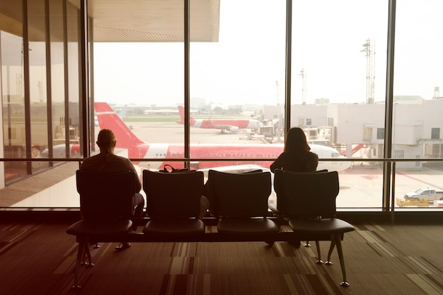 Man and woman at airport waiting for departure , color filter image , business travel airport