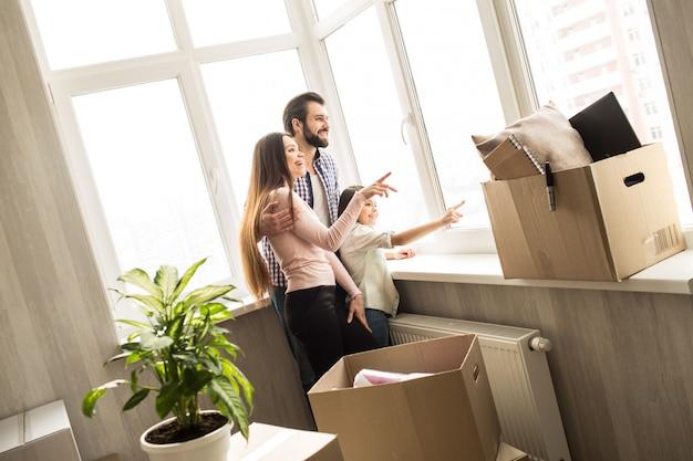 Мужчина, женщина и ребенок стоят перед большим окном и смотрят на улицу. женщина и ребенок, указывая на окна. они выглядят счастливыми. человек стоит рядом с ними. есть коробки с вещами.
