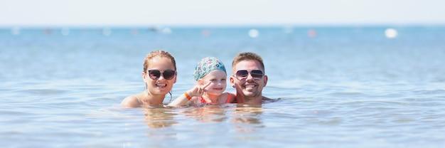 Мужчина женщина и ребенок плавают в море