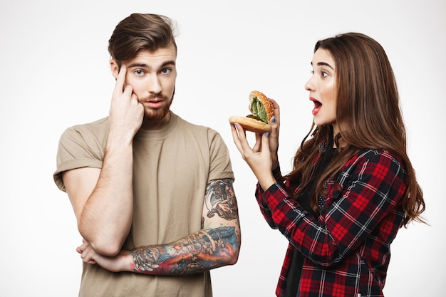 Man , woman annoying guy, playing with burger.