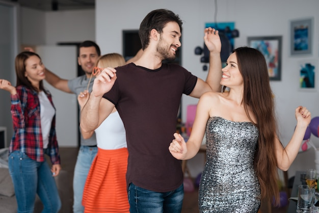 A man and a woman are dancing at a home party.