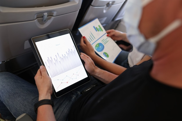 Man and woman are flying in airplane wearing protective masks with digital tablet and documents in their hands closeup