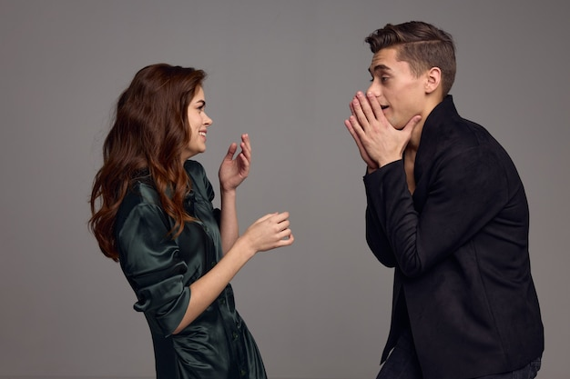 A man and a woman are gesturing with their hands and looking at each other on a gray background. high quality photo
