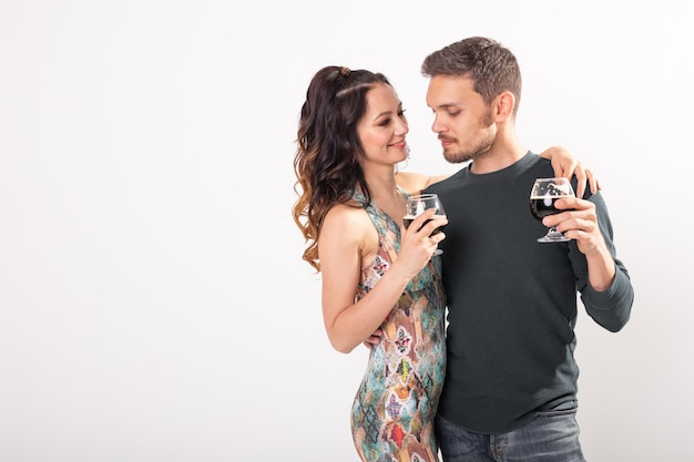 Man and woman are holding glasses of dark beer on white wall with copy space. oktoberfest concept.