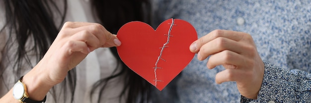 Man and woman are holding glued heart family relationship problems concept