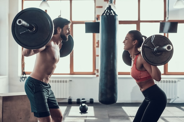 Man and woman are lifting barbells in the gym.