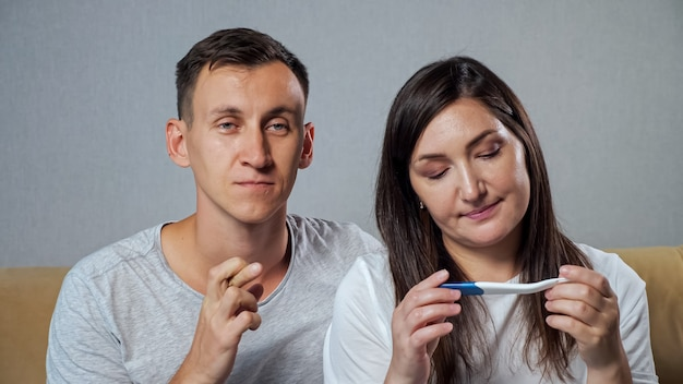 Man and woman are looking forward to the result of a pregnancy test. happiness of upcoming parenthood.