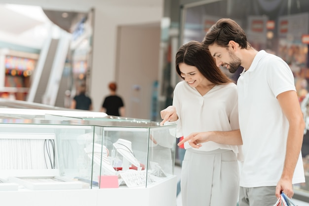 Man and woman are looking at jewelry in kiosk.
