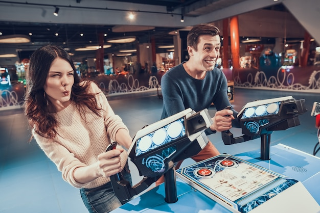 Man and woman are piloting blue aircrafts playing in arcade.