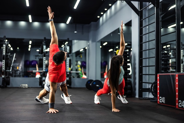 The man and the woman are in the plank position with their arms raised and doing exercises for the whole body and body stability.