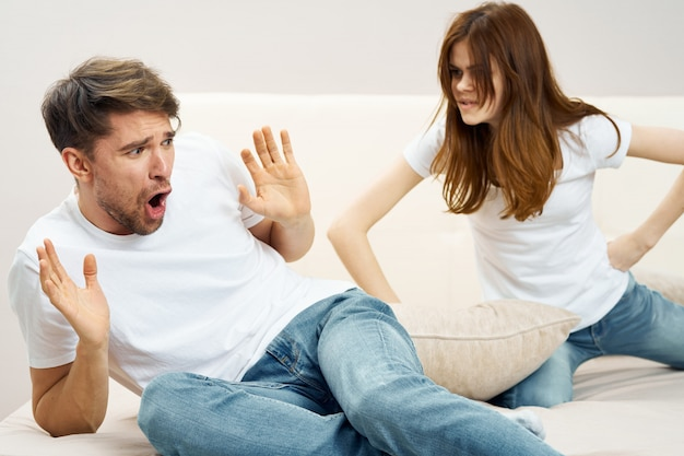 A man and a woman are sitting on the bed and talking about a relationship, a real quarrel