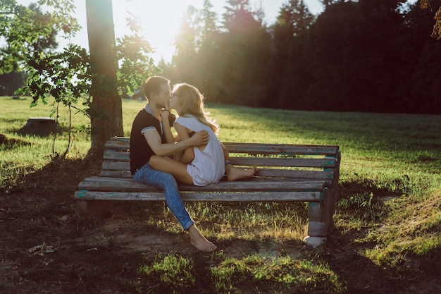 A man and a woman are sitting on a bench and kissing