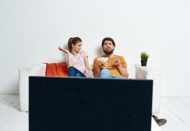 A man and a woman are sitting on the couch in front of the tv and a green flower in a pot