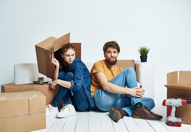 A man and a woman are sitting on the floor boxes with things moving renovation in a new apartment
