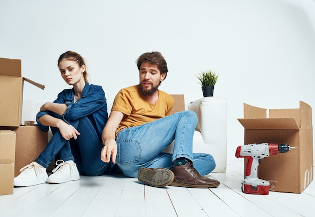 A man and a woman are sitting on the floor indoors near the couch and moving boxes.
