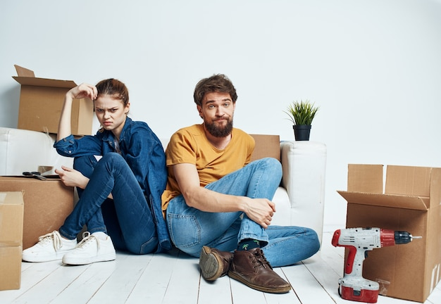 A man and a woman are sitting on the floor with open boxes and tools for repair