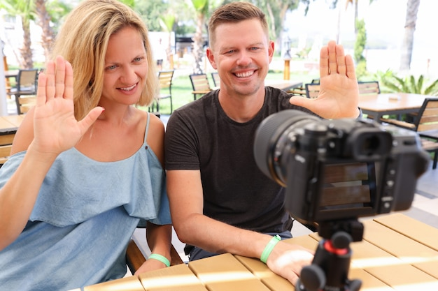Man and woman are sitting at table in bar and waving at camera