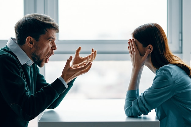 A man and a woman are sitting at a table talking, quarreling with each other, a real quarrel, household issues