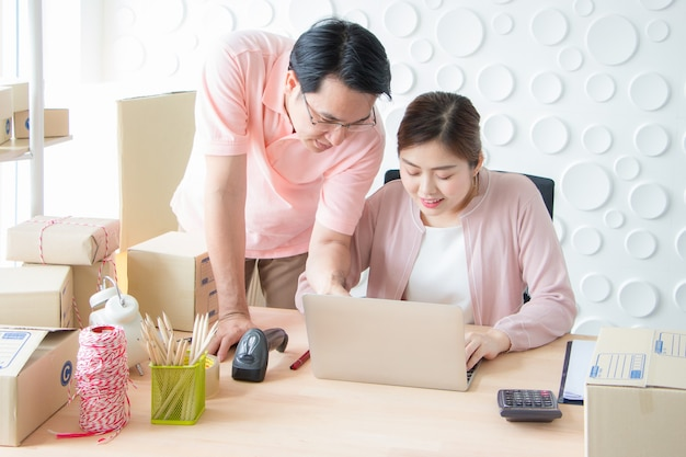 A man and a woman are smiling and looking at a notebook computer.