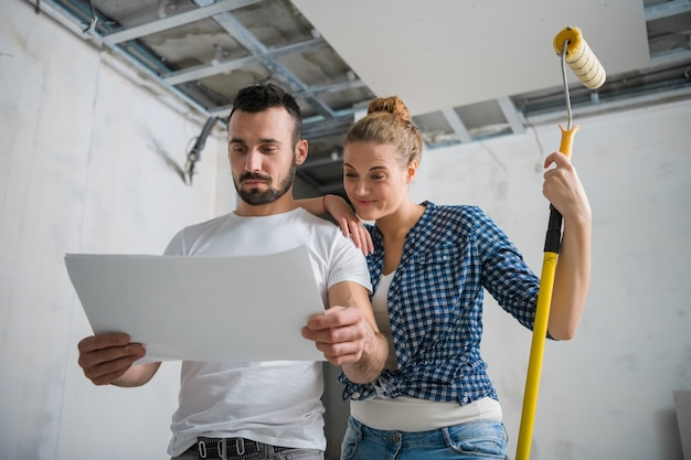 A man and a woman are smiling and looking at the work plan during the renovation of an apartment